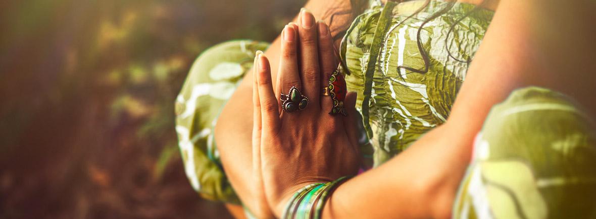 Frau in grünem Kleid und indischem Schmuck praktiziert Yoga