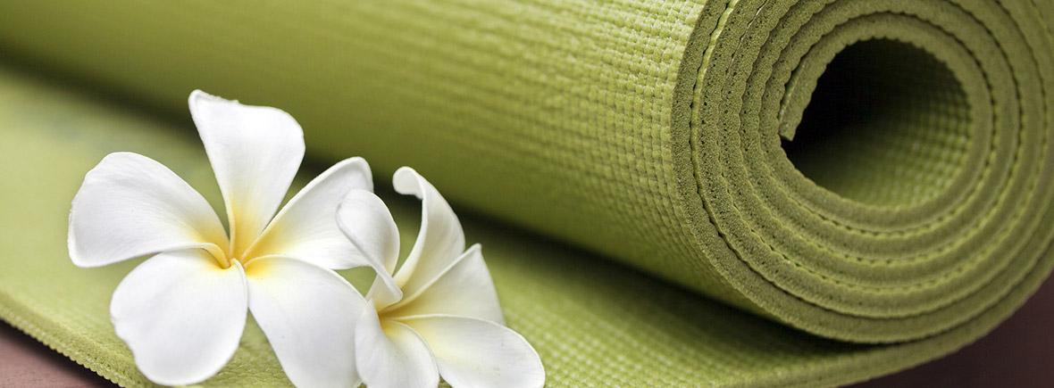 grüne Yogamatte mit weissen Frangipani-Blüten