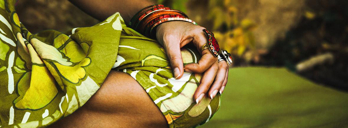 indische Frau mit grün gemustertem Kleid praktiziert Yoga