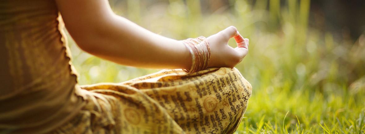 Yoga praktizierende Frau sitzt im Gras